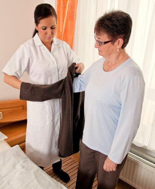 caregiver help her patient to dress-up