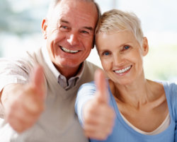 Portrait of a older couple showing thumbs up